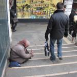 【写真】寒い日に路上に座る女性