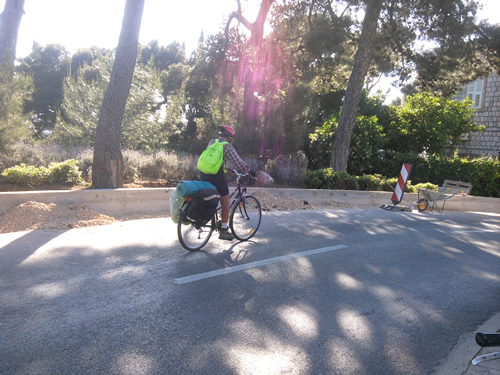 【写真】荷物を積んだ自転車で走るエリザベスさんの後姿。