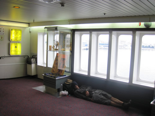 【写真】船内でゴロリと横になる旅行者。
