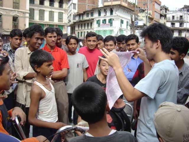 【写真】2003年 ネパール人に囲まれて手品をする様子。