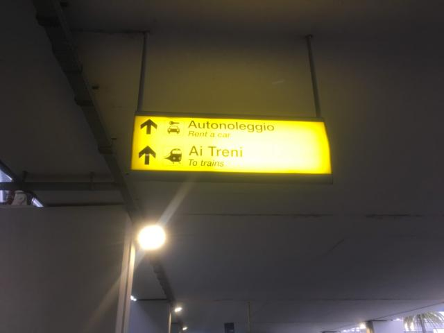 【写真】空港内に鉄道駅への案内がある「Ai Treni」の表示の方へ