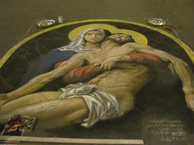 マドンナーロ 完成した絵の脇に投げ銭用の器をおいて置く。